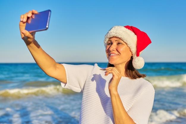 Gelukkige vrouw in kerstmuts op strand
