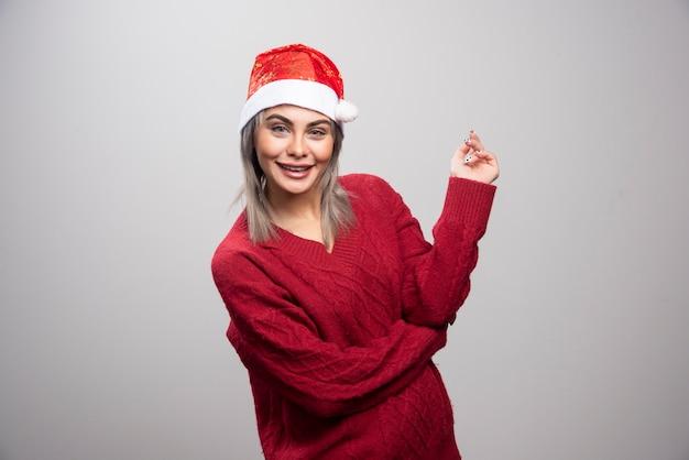 Gelukkige vrouw in kerstmuts staande op een grijze achtergrond.