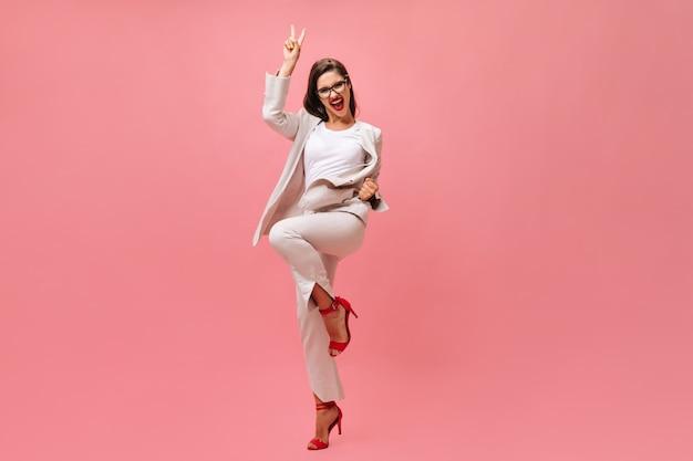 Gelukkige vrouw in kostuum dat vredesteken op roze achtergrond toont. vrolijke mooie dame in trendy mode-outfit verheugt zich op camera.