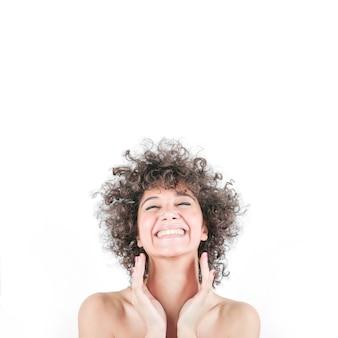 Gelukkige vrouw in krullend haar dat over witte achtergrond wordt geïsoleerd