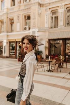 Gelukkige vrouw in licht overhemd en spijkerbroek in de stad. moderne vrouw met kort haar en heldere lippen lachend op straat.