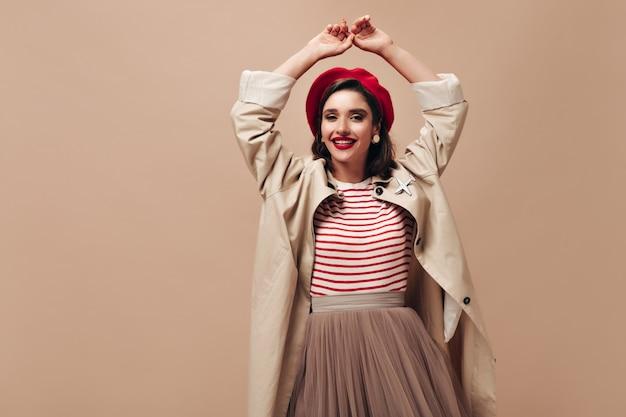 Gelukkige vrouw in loopgraaf en stijlvolle baret dansen op beige achtergrond. charmant meisje in gestreepte trui, rok en lange jas glimlacht.