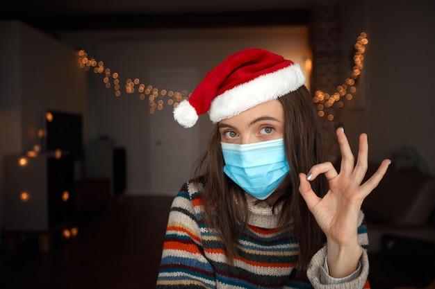 Gelukkige vrouw in medisch masker en kerstmanhoed die ok tijdens kerstmisviering thuis gebaren
