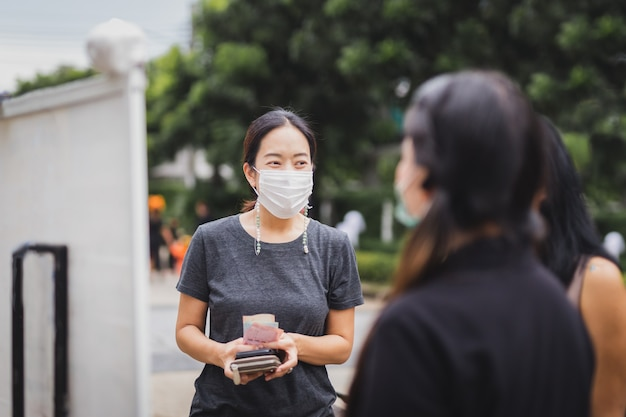 Gelukkige vrouw in medische beschermende maskers die zich met vrienden op straat bevinden die op afhaalmaaltijden wachten.