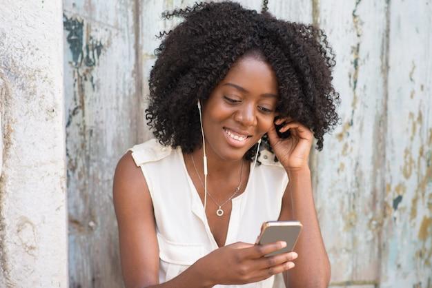 Gelukkige vrouw in oortelefoon genieten van muziek op de telefoon