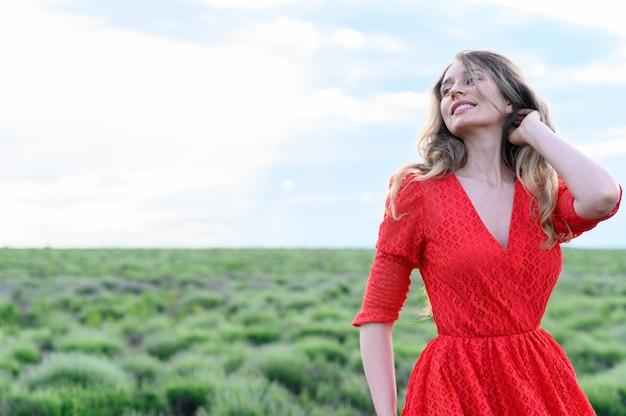 Gelukkige vrouw in rode jurk dansen en springen in lavendel veld