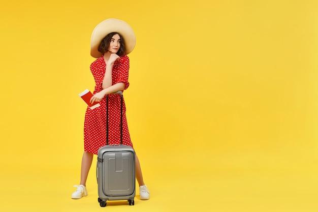 Gelukkige vrouw in rode jurk met grijze koffer en en paspoort gaan reizen op gele achtergrond. kopieer ruimte