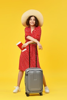 Gelukkige vrouw in rode jurk met grijze koffer gaan reizen op gele achtergrond.