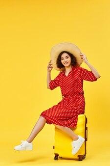 Gelukkige vrouw in rode jurk met koffer gaan reizen op gele achtergrond. concept van reizen.