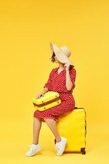 Gelukkige vrouw in rode jurk met koffer gaan reizen op gele achtergrond.