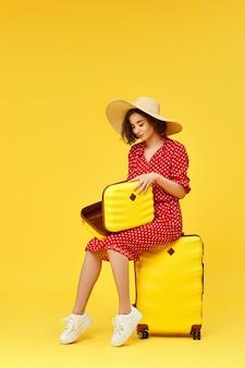 Gelukkige vrouw in rode jurk met open koffer gaan reizen op gele achtergrond.