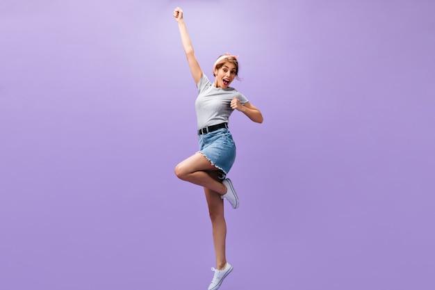 Gelukkige vrouw in rok en overhemd springt op paarse achtergrond. blij jong meisje in goed humeur in stijlvolle outfit poseren. n geïsoleerde achtergrond.