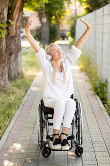 Gelukkige vrouw in rolstoel met hoofdtelefoons