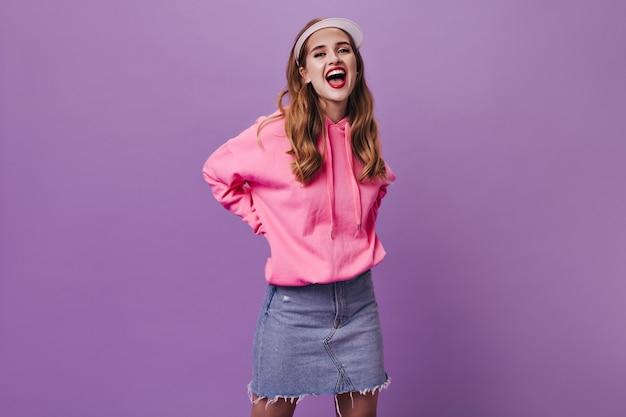 Gelukkige vrouw in roze outfit en pet glimlachend op paarse muur