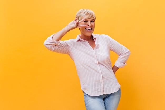 Gelukkige vrouw in roze outfit glimlacht en toont vredesteken op oranje achtergrond