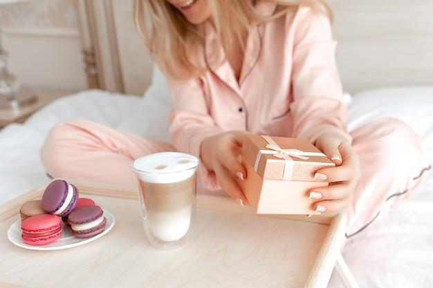 Gelukkige vrouw in roze pyjama's op witte deken met een huidige doos in haar handen