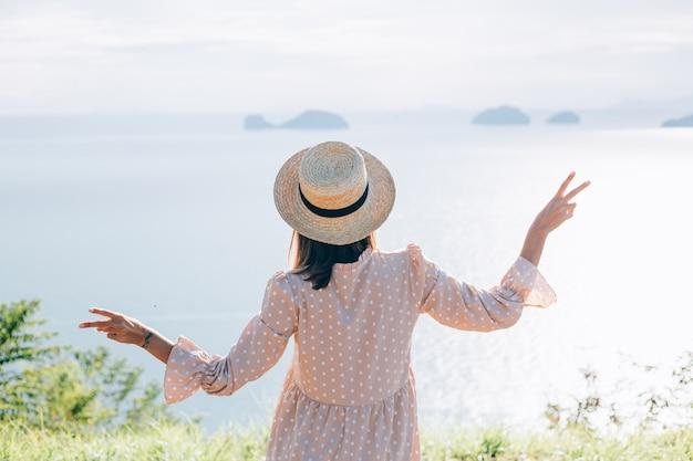Gelukkige vrouw in schattige zomerjurk en strohoed op vakantie met tropische exotische uitzichten