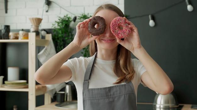 Gelukkige vrouw in schort houdt donuts voor haar ogen in de keuken