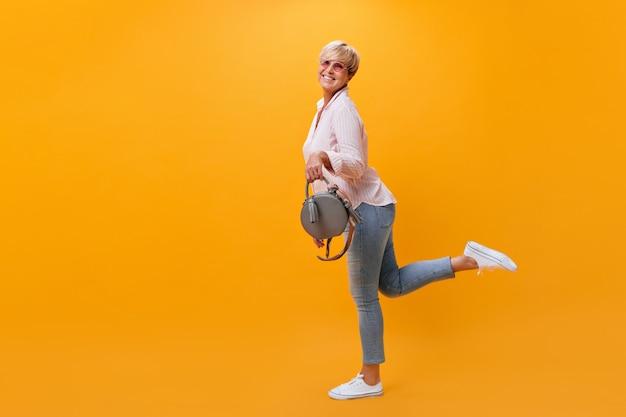 Gelukkige vrouw in spijkerbroek met plezier op een oranje achtergrond