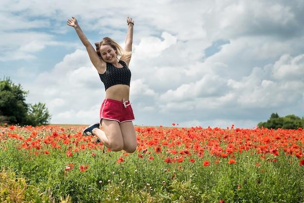 Gelukkige vrouw in sportkleren springen in papaverveld in warme zomerdag. vrijheid levensstijl