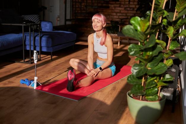 Gelukkige vrouw in stijlvolle top en korte broek rust na training in de buurt van mobiele telefoon thuis