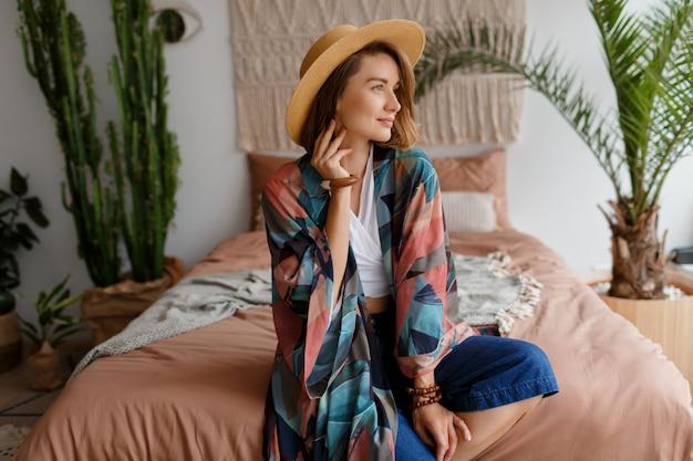 Gelukkige vrouw in strohoed die in boheemse slaapkamer situeert
