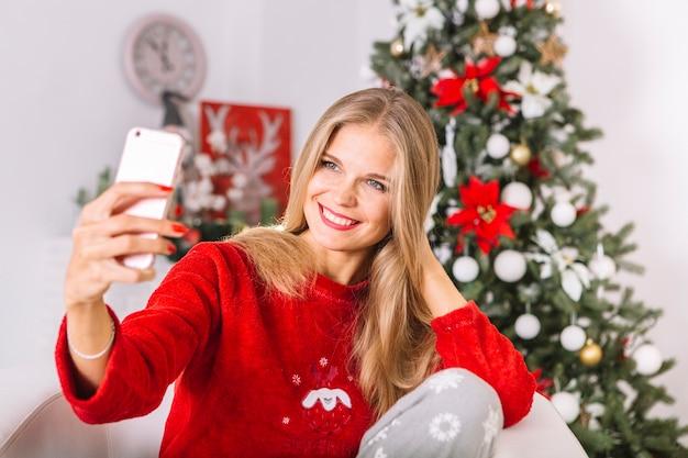 Gelukkige vrouw in sweater die selfie neemt