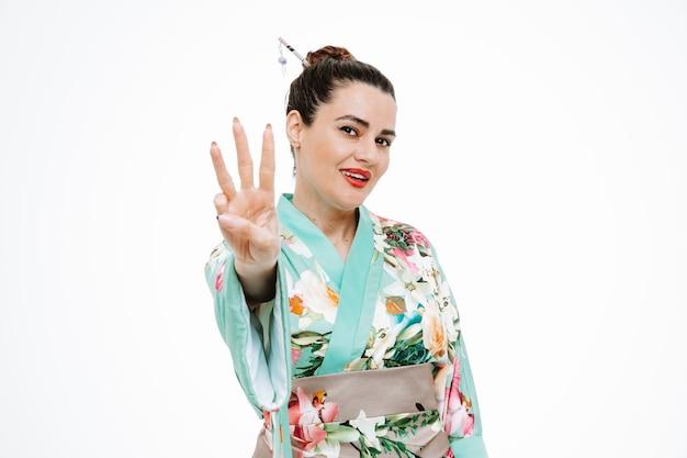 Gelukkige vrouw in traditionele japanse kimono blij en vrolijk nummer drie met vingers op wit tonen