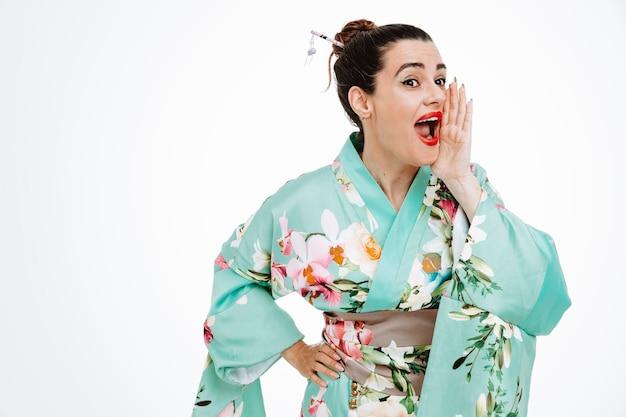 Gelukkige vrouw in traditionele japanse kimono die schreeuwt of iemand belt die hand in de buurt van de mond op wit houdt?