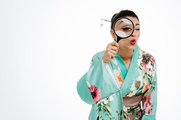 Gelukkige vrouw in traditionele japanse kimono met vergrootglas kijkend door glas met nieuwsgierigheid op wit