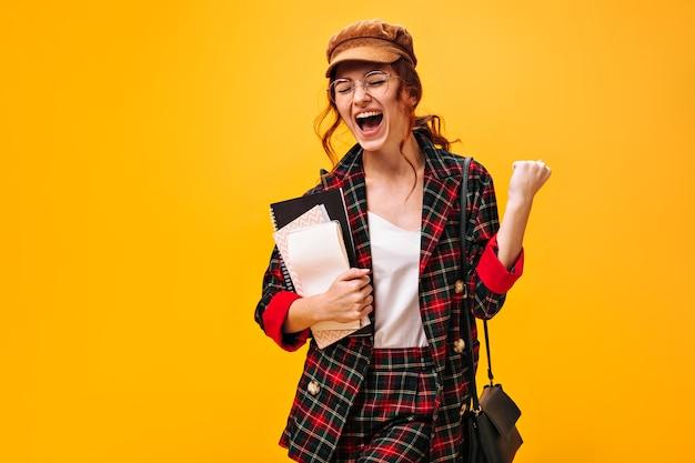 Gelukkige vrouw in trendy pak poseert emotioneel met notitieboekjes op oranje muur