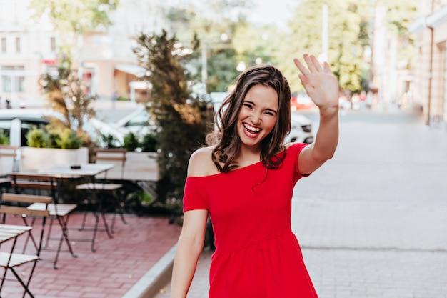 Gelukkige vrouw in trendy rode jurk zwaaiende hand. buiten schot van positieve mooi meisje wandelen door straat café.