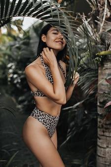 Gelukkige vrouw in trendy zwembroek camera kijken op natuur achtergrond. buiten schot van slanke gebruinde vrouw in exotische resort.