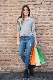 Gelukkige vrouw in vrijetijdskleding met het winkelen pakketten