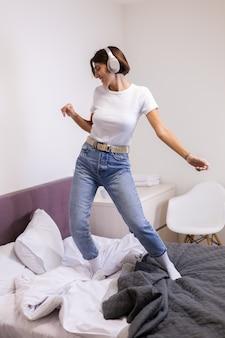 Gelukkige vrouw in vrijetijdskleding thuis in slaapkamer luistert naar muziek in hoofdtelefoons, dansen en springen