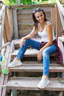 Gelukkige vrouw in vrijetijdskleding zit op de trap op de veranda en glimlachend kaukasisch meisje in een w...