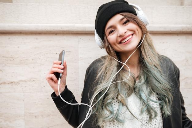 Gelukkige vrouw in warme kleren luisteren muziek op straat