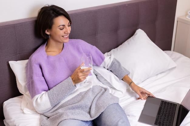 Gelukkige vrouw in warme trui in bed met een glas wijn alleen door haarzelf rusten kijken film komedie glimlach lachen