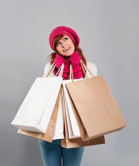 Gelukkige vrouw in winterkleren met papieren boodschappentassen
