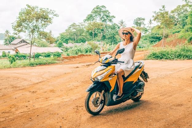 Gelukkige vrouw in witte jurk en zonnebril motor rijden