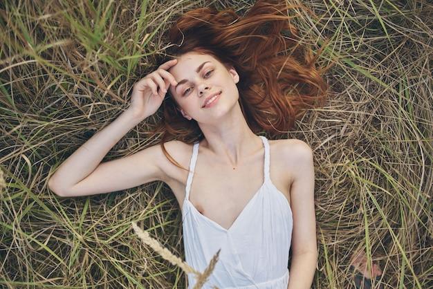 Gelukkige vrouw in witte jurk ligt op droog gras in de natuur bovenaanzicht