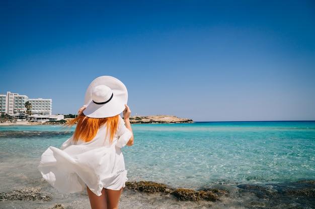 Gelukkige vrouw in witte kleren die zich op strand met glashelder water bevinden
