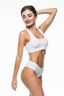 Gelukkige vrouw in witte ondergoedpasvorm die op witte muur wordt geïsoleerd
