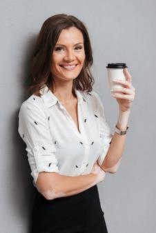 Gelukkige vrouw in zakelijke kleding poseren in de buurt van de muur met koffie op grijs