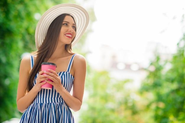 Gelukkige vrouw in zomerjurk poseren met strooien hoed