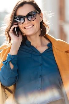 Gelukkige vrouw in zonnebril praten op mobiele telefoon
