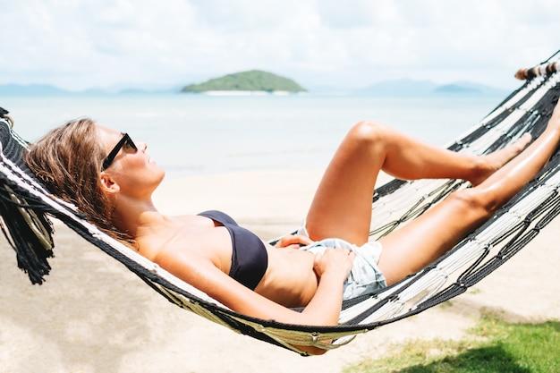 Gelukkige vrouw in zwarte bikini en korte broekjeans ontspannen in hangmat op tropisch strand