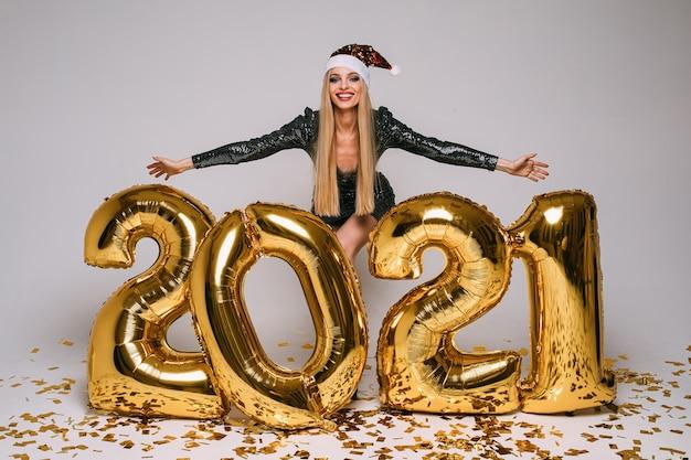 Gelukkige vrouw in zwarte cocktailjurk verheugt zich met grote gouden ballonnen 2021