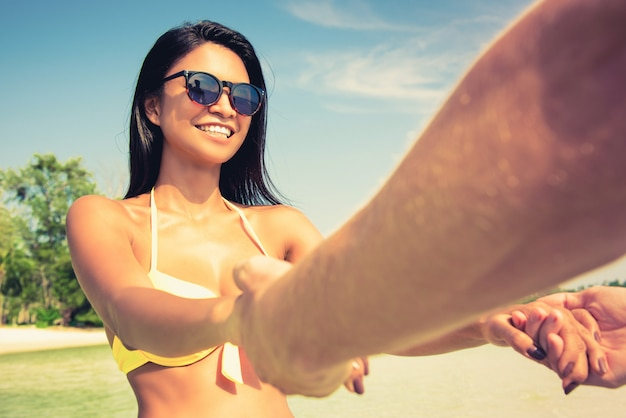 Gelukkige vrouw in zwempak die handen van haar vriend trekken, die van de tijd van de de zomervakantie genieten bij het strand