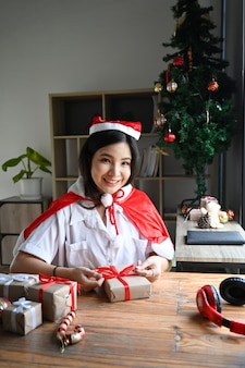 Gelukkige vrouw kerstcadeau versieren en glimlachen naar de camera.